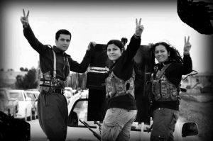 Image of three YPJ militiawomen waving